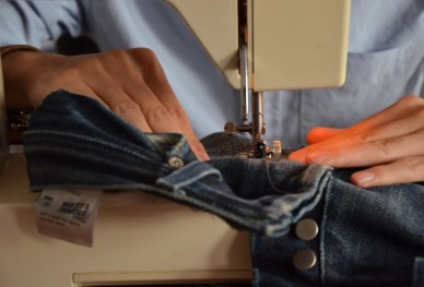 Feed the jeans and guide it through evenly!